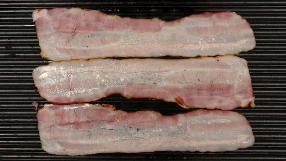 Thumbnail for Frying A Strips Af Bacon On A Black Pan