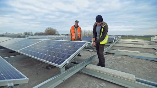 Installing the photovoltaic panels. Solar panel technician installing solar panels