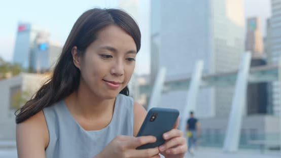 Femme regarder le téléphone intelligent à l'extérieur
