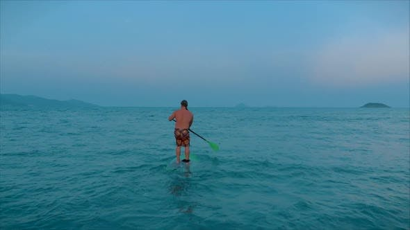 Ssurfer Is Waiting for His Wave To Surf, the Surfer Controls the Oar While Standing on the Surfboard