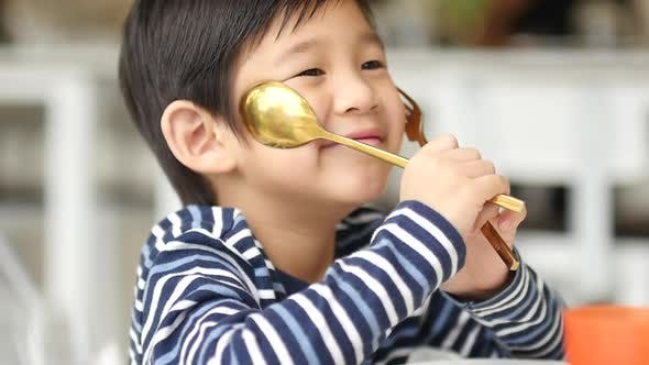 Cute Asian Child Holding A Spoon And Fork