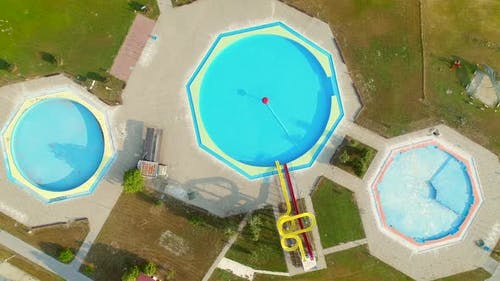 Aerial view of empty pools with slides in abandoned aqua park.