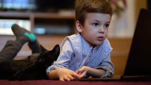 Lustiges Kind mit Kätzchen mit einem Laptop zu Hause.