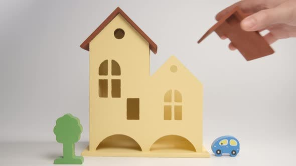 Thumbnail for Menschliche Hand setzt ein Dach auf ein Spielzeughaus
