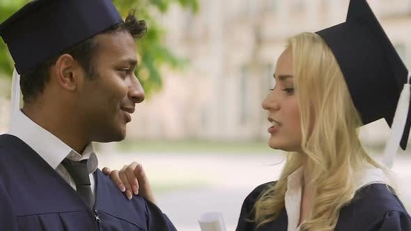 Thumbnail for Blonde girl adjusting tie to her biracial classmate before graduation ceremony