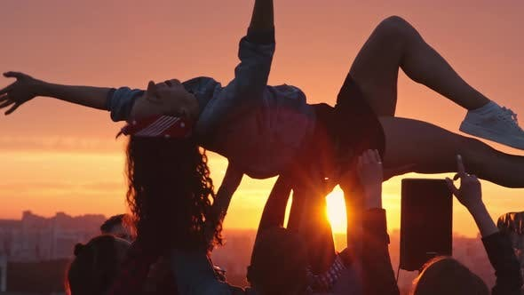 Thumbnail for Friends Lifting Birthday Girl Up at Sunset