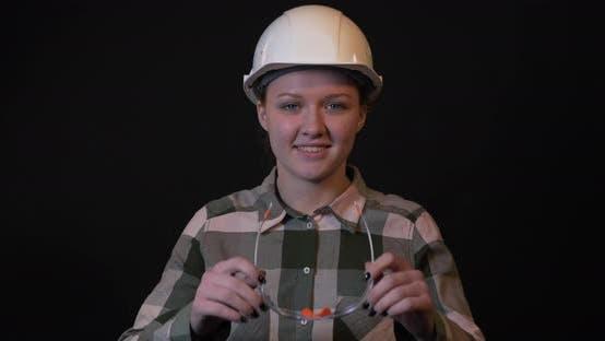 Thumbnail for Junge weibliche Ingenieurin setzt Schutzbrille an.