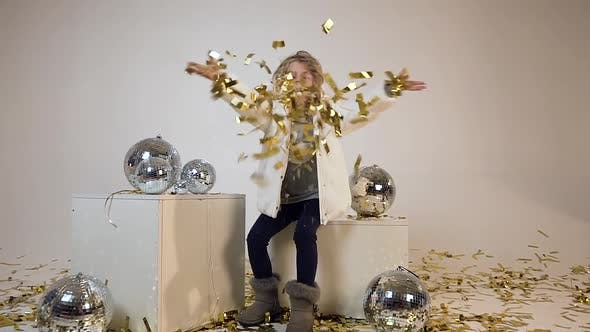 Thumbnail for Pretty Joyful Teen Model in Fashion Clothes Sitting Near Disco Balls and Blowing Golden Confetti