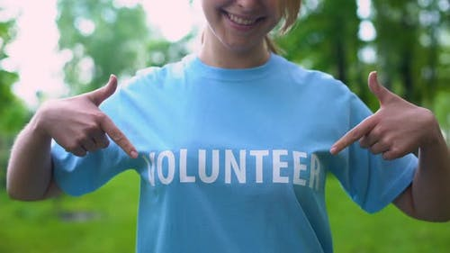 Cheerful Young Woman Pointing at Volunteer Word on T-Shirt, Responsibility