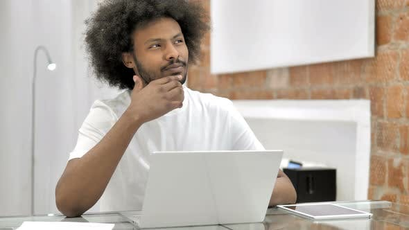 Thumbnail for Denkender afrikanischer Mann arbeitet auf Laptop