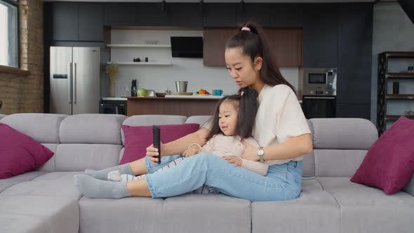 Lovely Mother and Child Using Smartphone on Couch