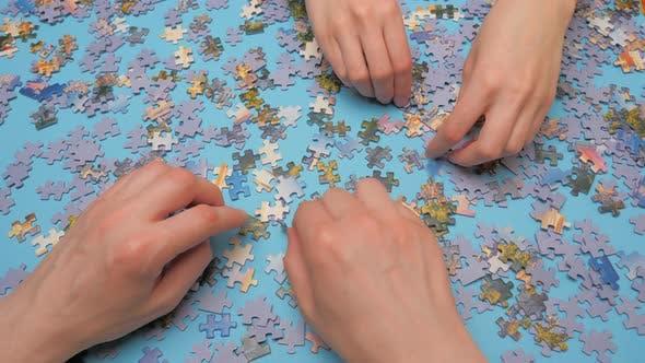 Zusammenbau Puzzle. Handpassende Puzzle-Hälften. Freizeit-Aktivität. Schritt für Schritt Liebe erreichen