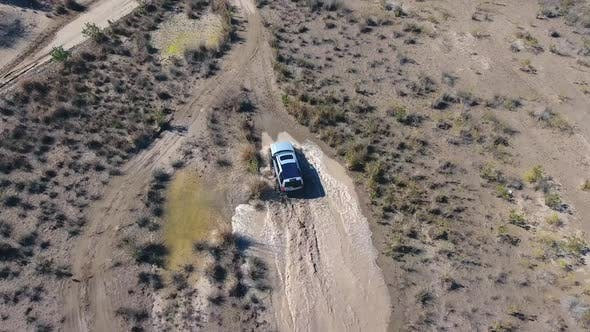 Thumbnail for Car is Aerial Following at Desert Puddle