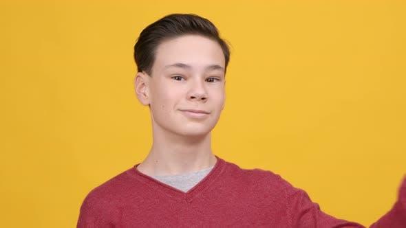 Teen Boy gestikuliert VSign Lächeln zur Kamera auf gelbem Hintergrund