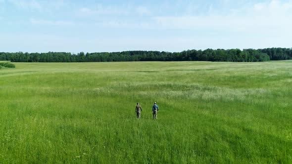 Thumbnail for Two Fisherman Walking Through Green Meadow