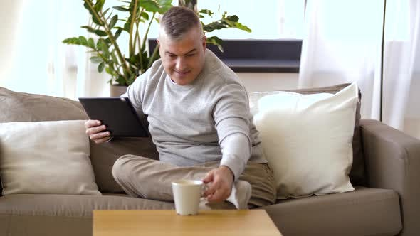 Thumbnail for Man with Tablet Pc Sitting on Sofa at Home