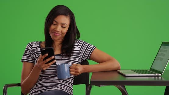 Thumbnail for Black woman messaging on phone while working on laptop at cafe on green screen