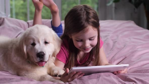 Thumbnail for Smiling Girl Watching Cartoon on Tablet with Puppy