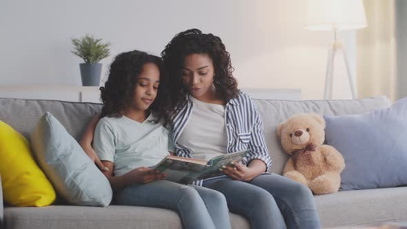 Loving African American Mother Reading Fairy Tale Book to Her Cute Little Daughter Embracing