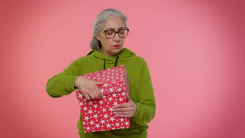 Elderly Granny Woman Opening Gift Box Expressing Disappointment Dislike Gesture to Awful Present