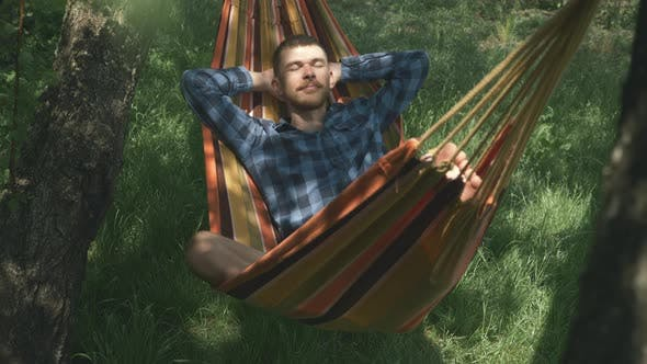 Thumbnail for Man sleeping in hammock outdoors. Carefree man relaxing in hammock on sunny summer day
