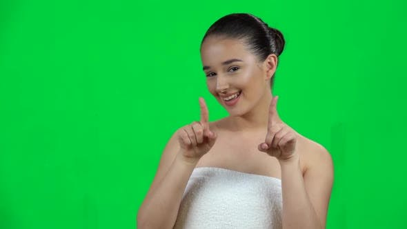 Thumbnail for Cute Girl Smiles and Showing Heart with Fingers Then Blowing Kiss on Green Screen at Studio. Slow