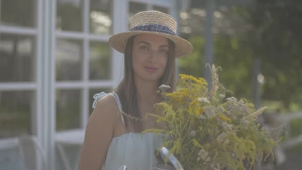 Thumbnail for Adorable Young Woman in Straw Hat and White Dress Looking at the Camera Smiling While Sniffing Wild