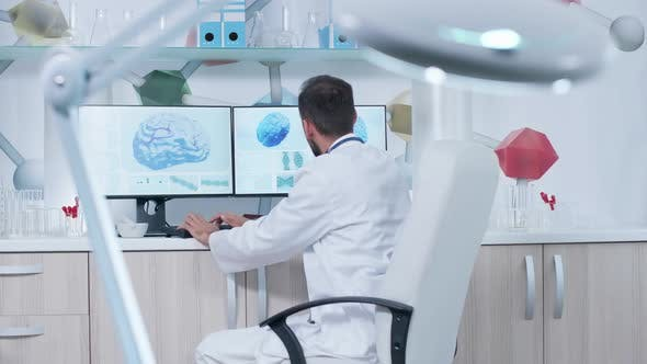 Thumbnail for Doctor in Modern Office or Research Center Working on a Computer with 3D Brain Scans
