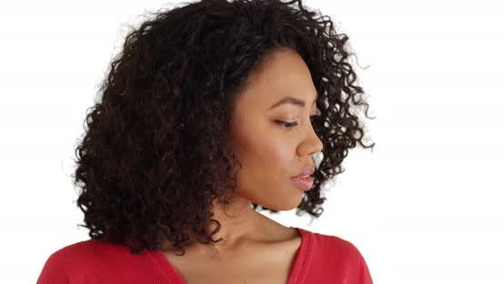 Portrait of pretty African woman looking at surroundings thoughtfully in studio