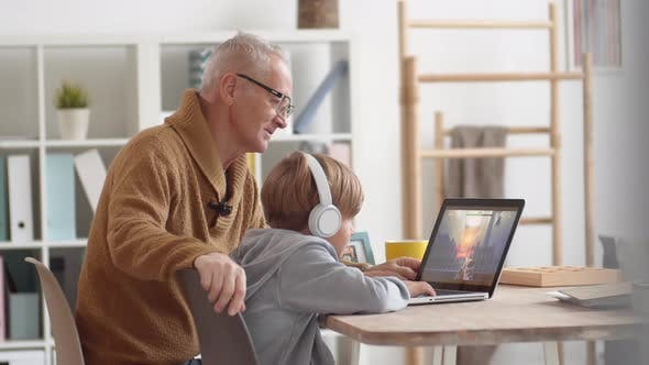Thumbnail for Aged Man Watching Grandson Playing Shooter