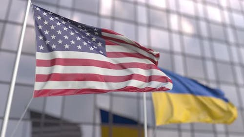 Waving Flags of the United States and Ukraine in Front of a Building
