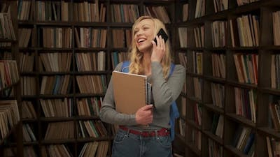 Female Student Talking on the Phone and Laughing in the Library