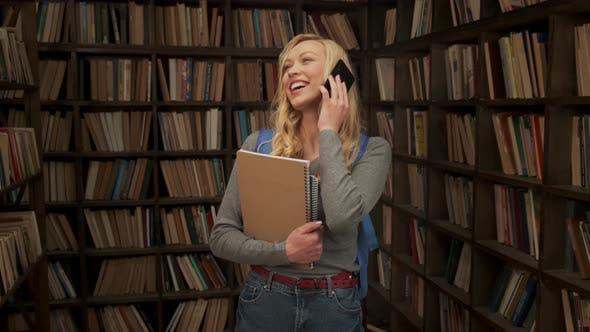 Studentin spricht am Telefon und lacht in der Bibliothek