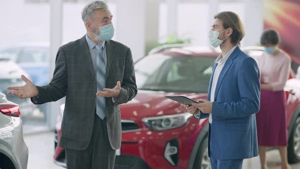 Young Dealer and Senior Buyer Talking in Showroom As Blurred Woman Choosing Automobile at Background