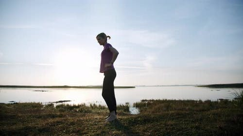 Silhouette of Young Sporty Woman Engaged in Gymnastics on Background Sky and Lake. V3
