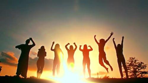 Silhouette von Freunden, die im Sonnenuntergang springen