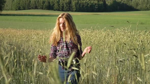 Thumbnail for Country Girl Farmer with Golden Hair Wearing a Checked Shirt Walking in Rye Field