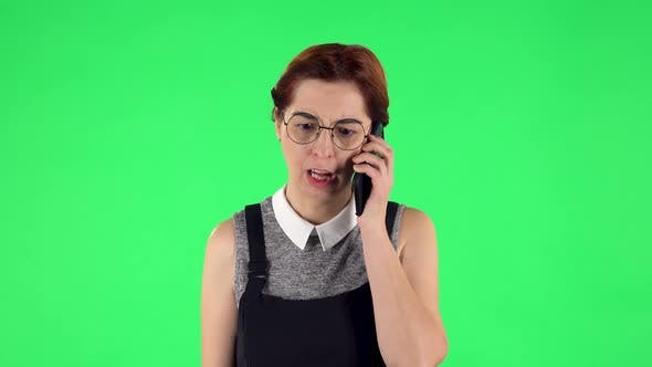Thumbnail for Portrait of Funny Girl in Round Glasses Is Angrily Talking for Mobile Phone, Proving Something