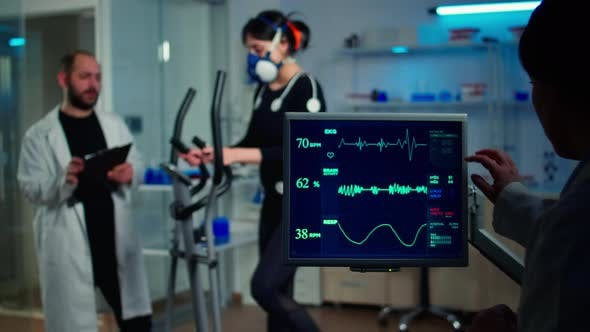 Specialist Sport Researcher Monitoring Heart Rate on Athlete