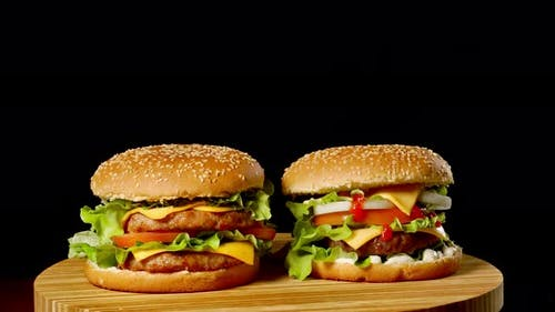 Two Craft Beef Burgers on Wooden Table Isolated on Dark Grayscale Background.