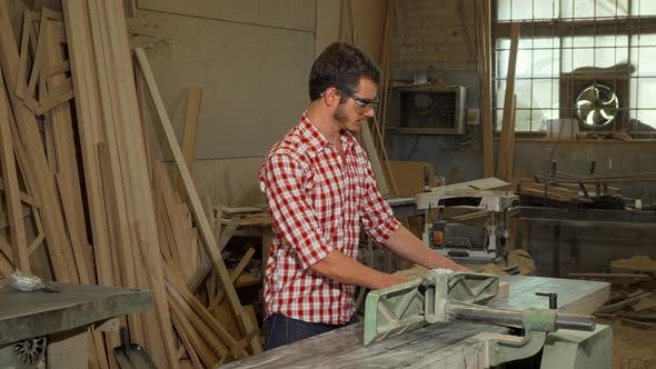 Thumbnail for Young Male Carpenter Grinding Wood Piece at His Workshop