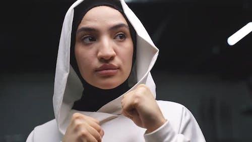 Arabischer Athlet ein Muslim steht in der Pose eines Kämpfers, der in einem Fitnesscenter mit einem Weiß boxt
