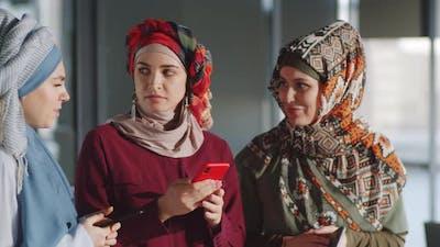 Businesswomen in Hijabs Using Smartphone and Speaking