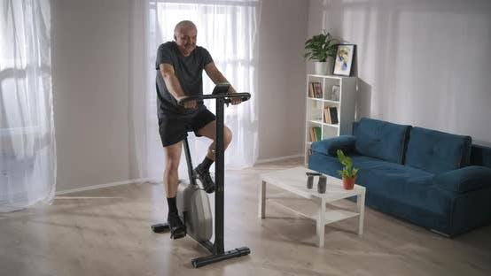 Modernes stationäres Fahrrad für das Training zu Hause Der Mann im mittleren Alter verwendet es, um sich fit zu halten und