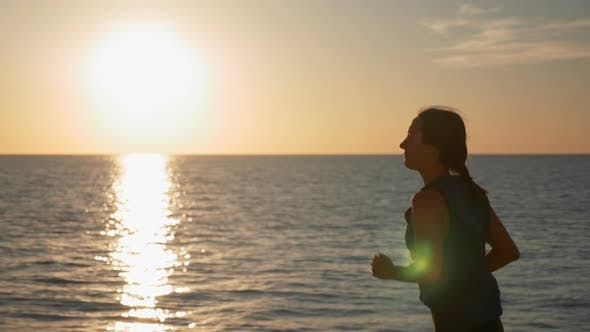 Thumbnail for Motivated fitness female in sportswear runs along beach promenade at sunset. Running concept