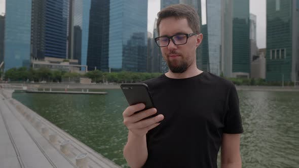Man with Cell Phone in Big City Sending Message