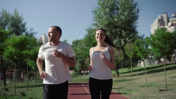 Thumbnail for Porträt eines lächelnden kaukasischen erwachsenen Mannes und einer Frau, die im sonnigen Sommer auf Laufstrecke joggen