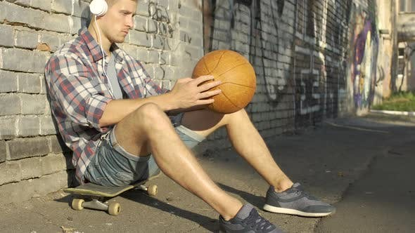 Thumbnail for Thoughtful Male Teen Sitting on Skateboard and Listening to Music in Headphones