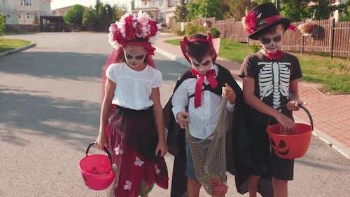 Kinder in Kostümen gehen die Straße hinunter, während Trick-oder-Behandlung