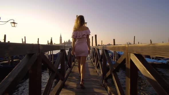 Girl Walking on the Water Deck Near Gondolas